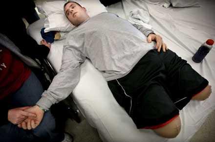 """""""JAG SKA GÅ IGEN"""" 24-årige Dennis Leonard får en sista uppmuntrande handtryckning från sin fru innan han ska försöka ta sig upp i rullstolen. Det är bara tre veckor sedan Dennis förlorade bägge sina ben i en så kallad IED-explosion vid en vägkant utanför Bagdad. Han gör sitt bästa för att vara tapper. """"Jag är glad att jag lever och jag vet att jag kommer att gå igen"""", säger han."""