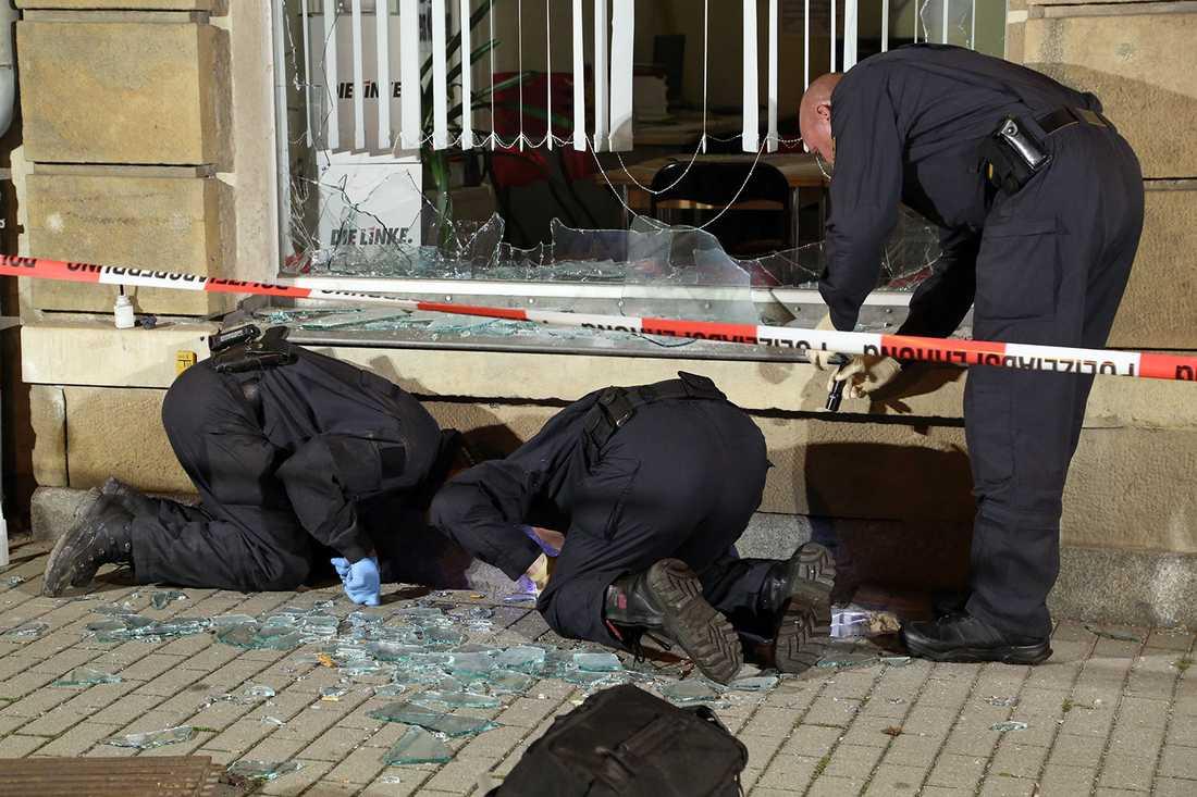 """Poliser undersöker utanför ett kontor tillhörande vänsterpartiet """"Die Linke"""" efter ett attentat."""