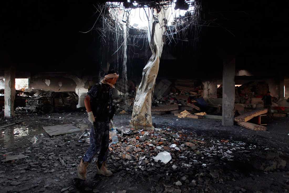 En man röjer bland bråte på platsen där många människor dog och skadades i ett bombanfall i jemens huvudstad Sanaa.