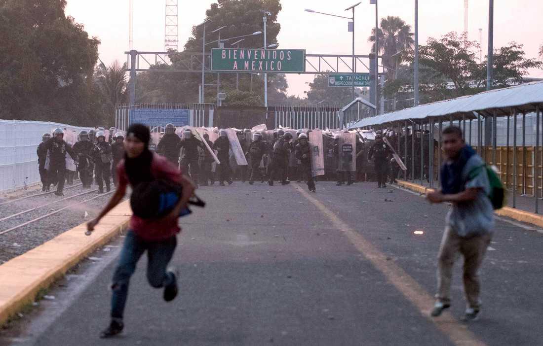 Migranter flyr från mexikanska poliser vid en sammandrabbning på en bro som binder samman Mexiko och Guatemala.