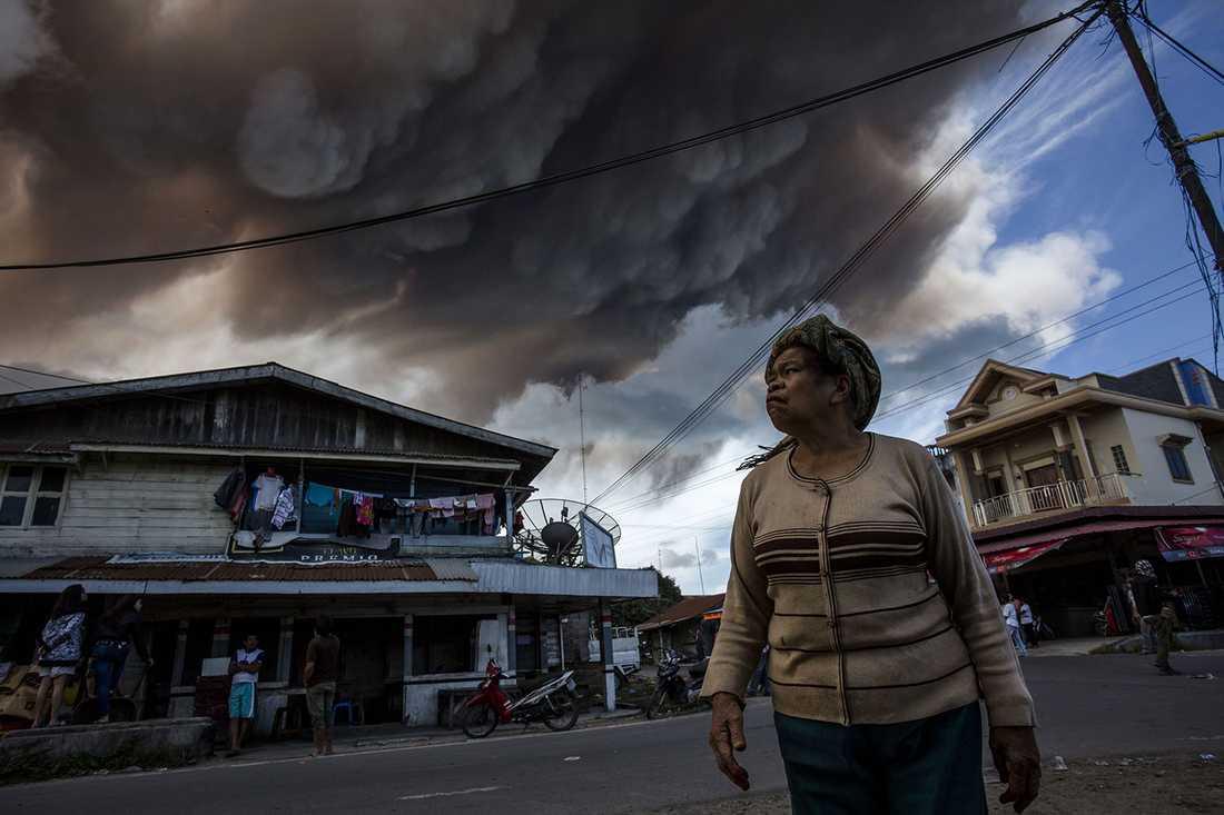 En kvinna tittar på ett stort rökmoln från vulkanen i byn Simpang Empat.