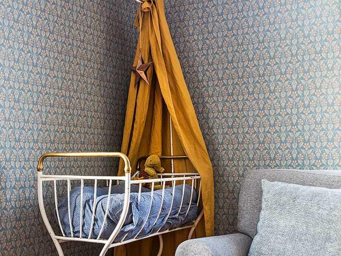 Alla tapeter i huset utom i matsalen är från Boråstapeters serie Anno. I vardagsrummet står en antik barnsäng åt Sixten.