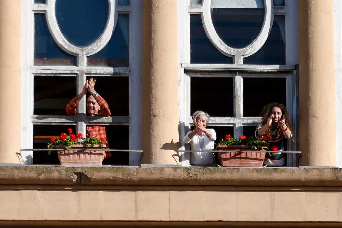 Några italienare i Rom klappar händerna för att fira att den långa tiden i karantän är över.