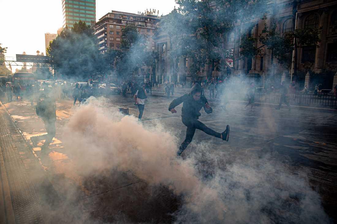 En demonstrant sparkar på en tårgasgranat under fredagens protester i Santiago.