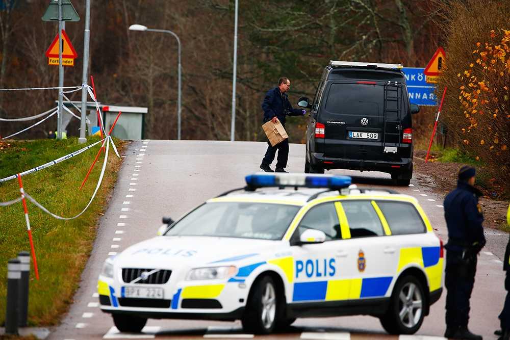 Polisens tekniker letar i ett dike vid vägen.