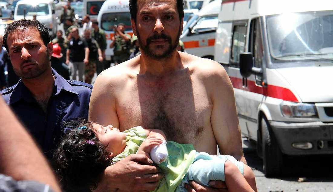 våldet fortsätter  I går dödades sju människor i en explosion i Syriens huvudstad Damaskus. Här syns en sårad flicka som bärs iväg av en man för att få hjälp.
