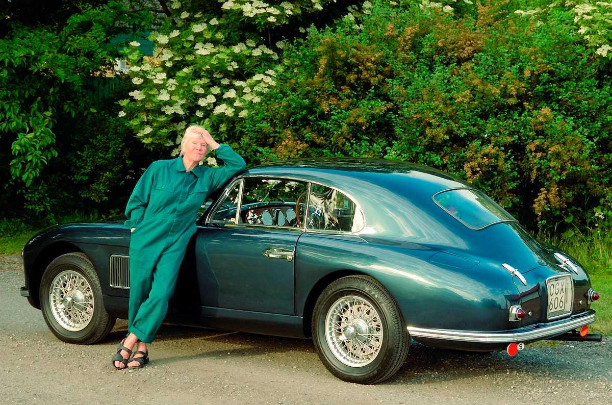 """Birgitta Stenberg framför en Aston Martin, iklädd overall och sandaler, precis som när hon mekade med sin egen Aston som ung. Just denna bil har faktiskt samma motor som satt i Birgittas. –Kamkedjan började skramla. Och eftersom gamla sportbilar var billiga, men reservdelarna dyra, så plockade jag i en Jaguarmotor i stället. Originalmotorn blev stående i ett garage hos en bekant, som många år senare sålde den vidare till en behövande. I Birgittas böcker """"De frånvända"""", """"Chans"""", """"Spanska trappan"""" och """"Skurkar"""" finns många fina bilupplevelser. De är samtidigt berättelser om denna nyfikna, sportbils-mekande, bisexuella, blondins brokiga liv i 1950- och 60-talets Europa."""