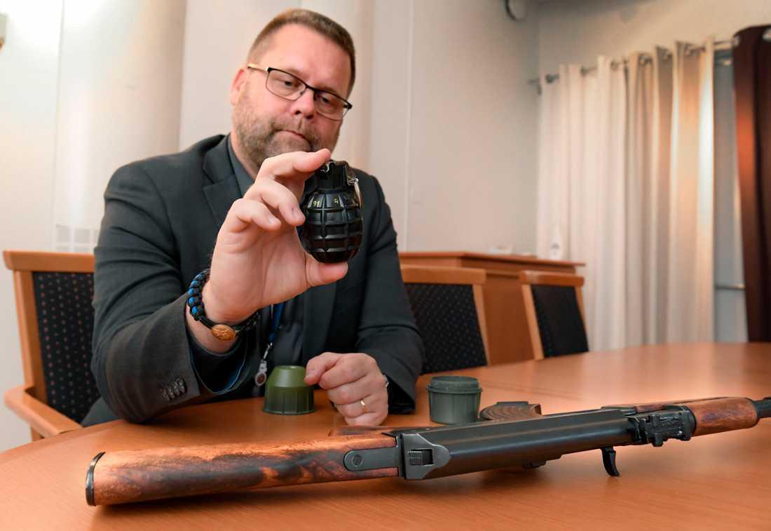 Polisens utredare Lars Bröms med en handgranat av den typ som dödade 63-åringen i Vårby gård i februari. Bredvid honom ligger en kalasjnikov – ett vapen som är vanligt förekommande i skjutningar.