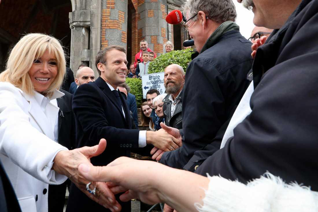 Frankrikes president Emmanuel Macron och hans hustru Brigitte Macron skakar hand med väljare efter att ha röstat i Le Touquet i norra Frankrike.