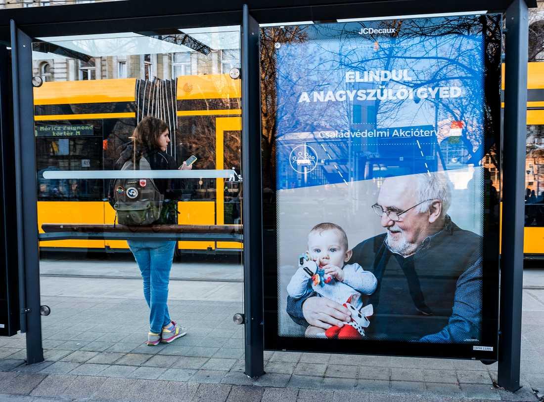 En affisch visar en äldre man med ett barnbarn i sina armar.
