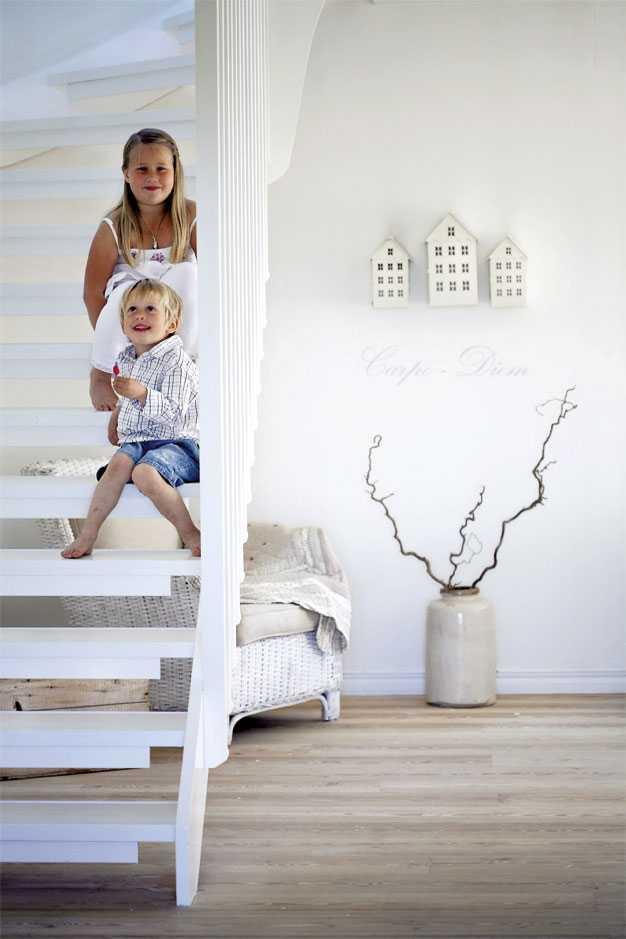 Mjuka färger i vitt, beige och brunt skapar harmoni i vardagsrummet. Trappan ringlar vit och luftig upp mot övervåningen, en perfekt utsiktsplats för Ebba och Viggo.