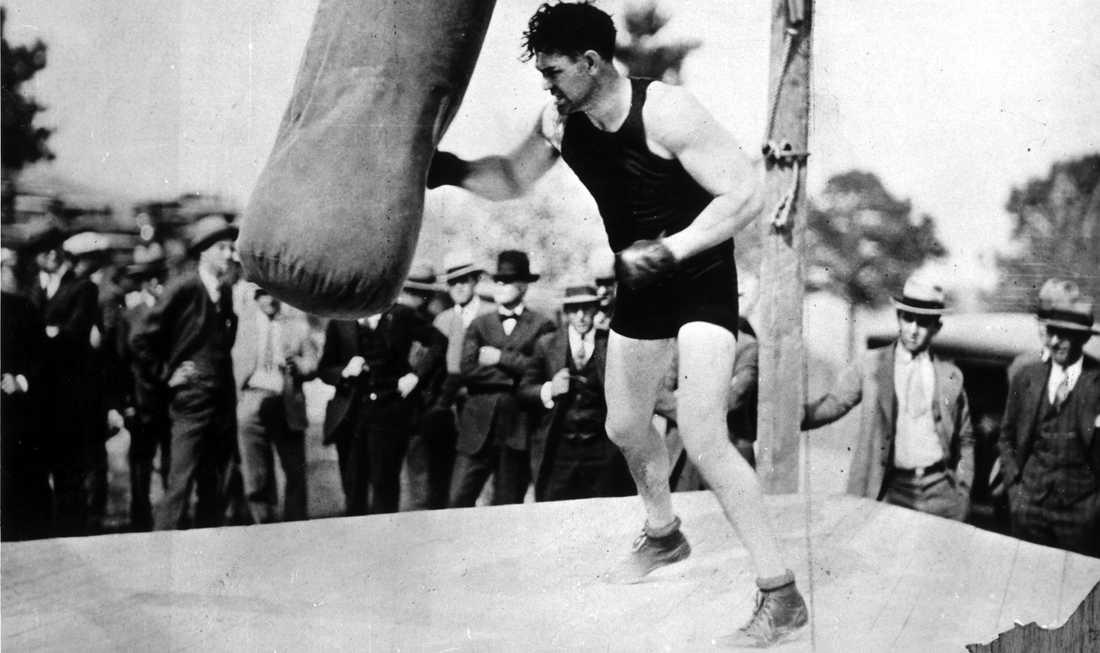 """Jack Dempsey (1895-1983) bearbetar sandsäcken inför nyfikna blickar. """"The Manassa Mauler"""" höll tungviktstiteln mellan åren 1919-1926. När Dempsey förlorade titeln mot Gene Tunney 1926 gjorde han det inför den största betalande boxningspubliken i historien – 120 000 åskådare."""