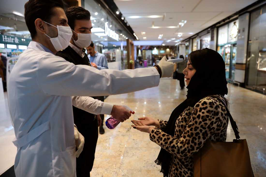 En kvinna får temperaturen mätt i ett köpcentrum i Teheran. Över 54000 fångar släpps för att minska risken för smittspridning i landets fängelser.