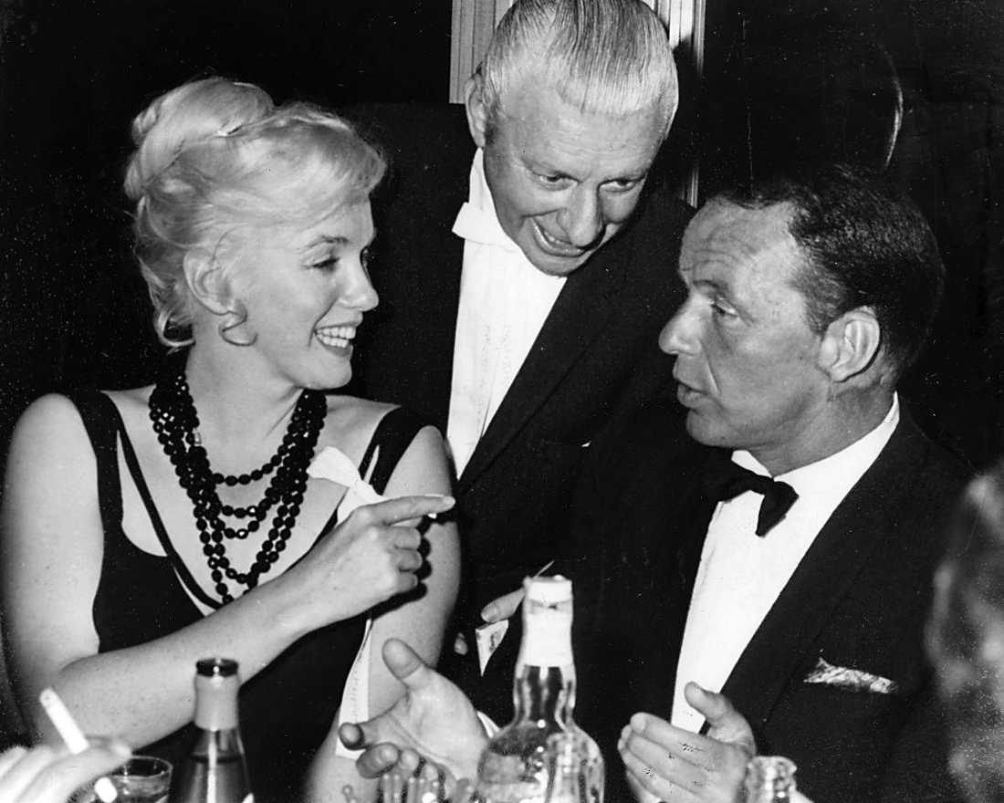 """""""FÖRSÖKTE RÄDDA HENNE"""" Marilyn Monroe och Frank SInatra (mannen i bakgrunden är okänd) vid samma bord 1959 på casinot Cal Nevada Lodge i Nevada, USA. """"Om hon blev hans fru trodde han att andra skulle låta henne vara och ge henne en chans att rycka upp sig"""", säger Sinatras chaufför George Jacobs i en ny bok. Foto"""