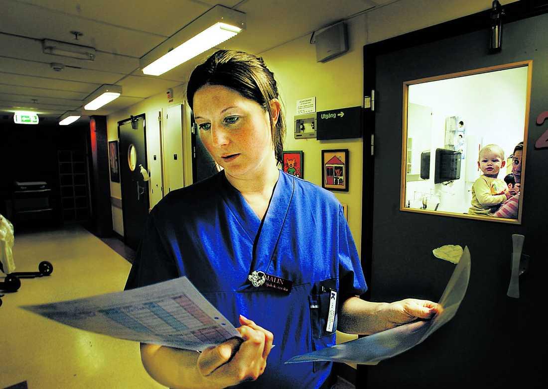 """Malin Håkansson gör sig redo att möta nästa patient. I bakgrunden skymtar Amina, 15 månader. Hon har just fått kortison mot utslag på ryggen. """"Alla är lika stridslystna nu. Vi ska löpa linan ut – vi ska få upp lönen"""", säger Malin."""