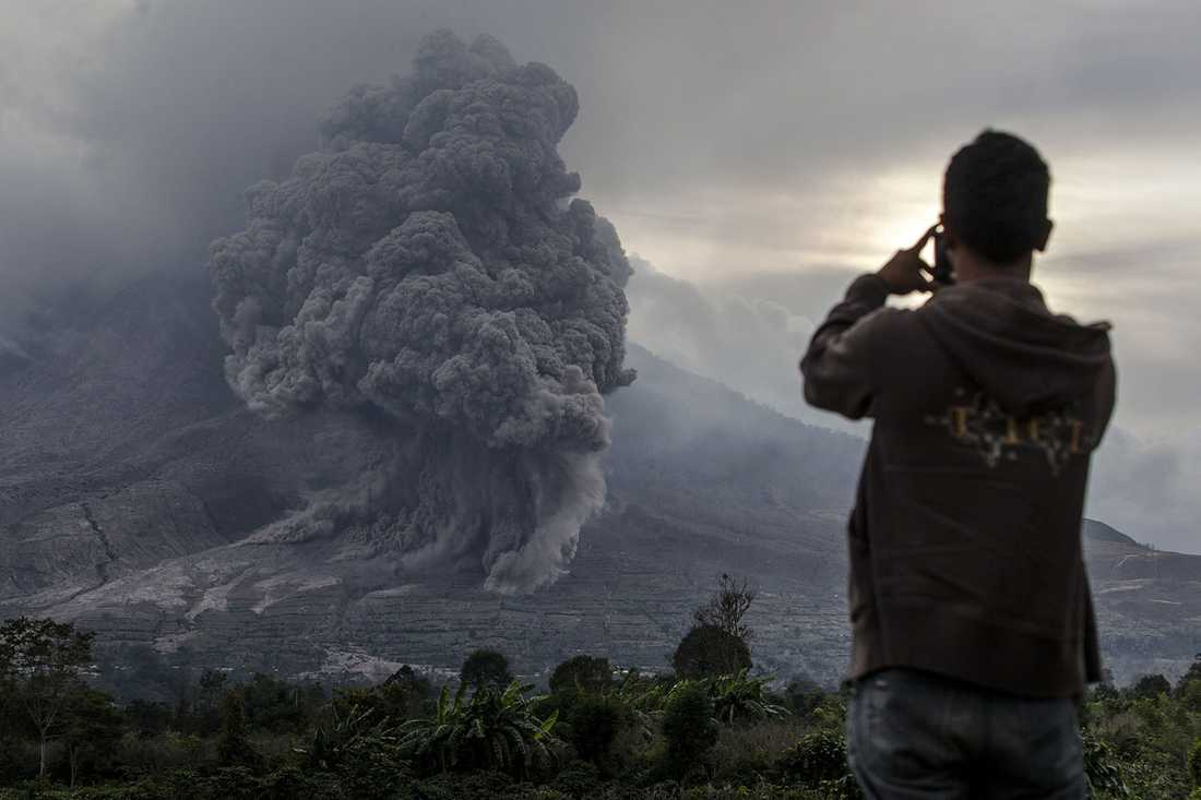 En man fotograferar Mount Sinabung.