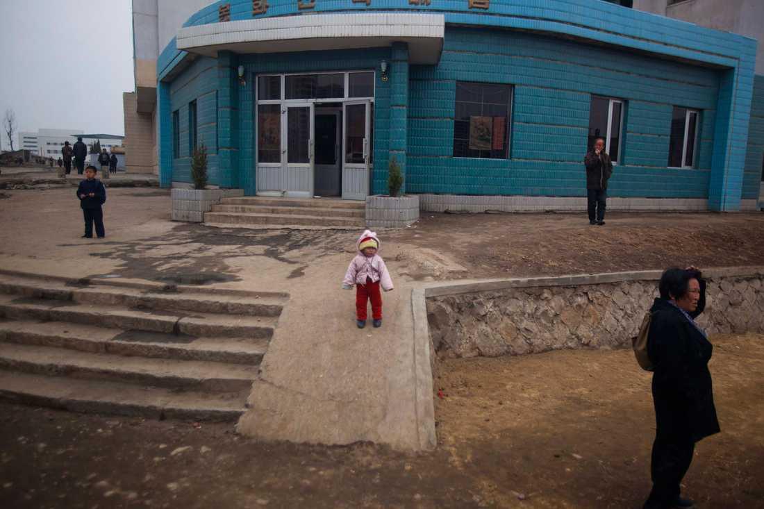 Invånare i Nordkoreas huvudstad Pyongyang. Gatan är inte asfalterad.