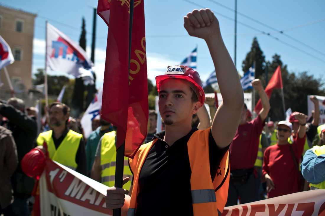 Förstamajfirare höjer sina nävar i Greklands huvudstad Aten 2019. I år blir det en annorlunda högtidsdag för världens arbetarrörelser. Arkivbild.