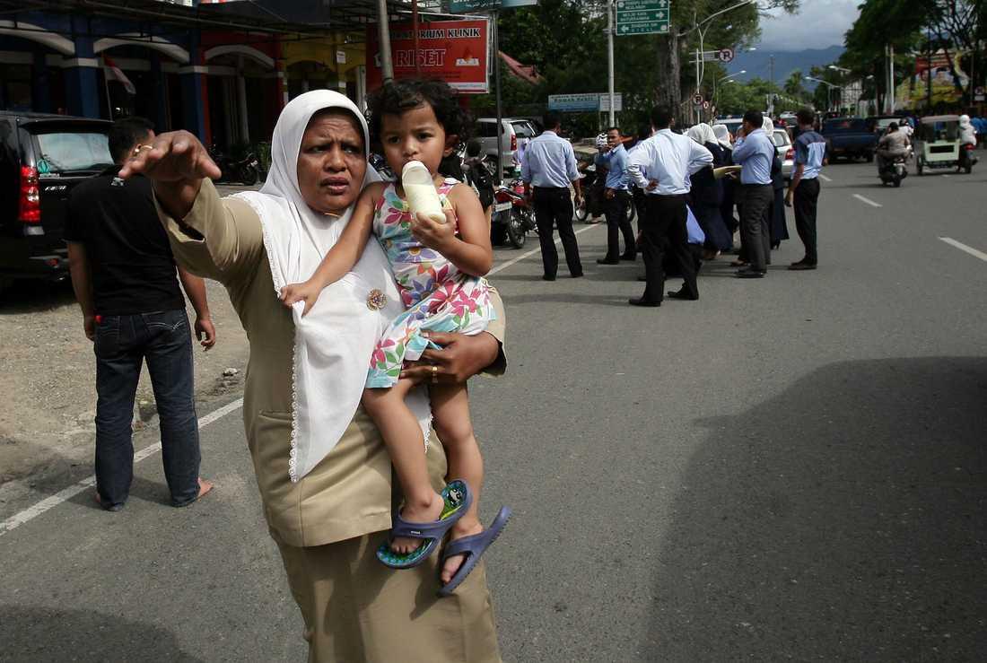 En kvinna med sitt barn försöker stoppa en bil för att lifta upp till högre höjder.