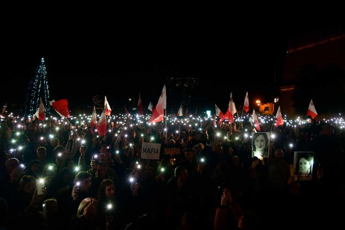 Demonstranter håller upp bilder av den mördade journalisten Daphne Caruana Galizia vid en demonstration utanför premiärministerns kansli på tisdagen.