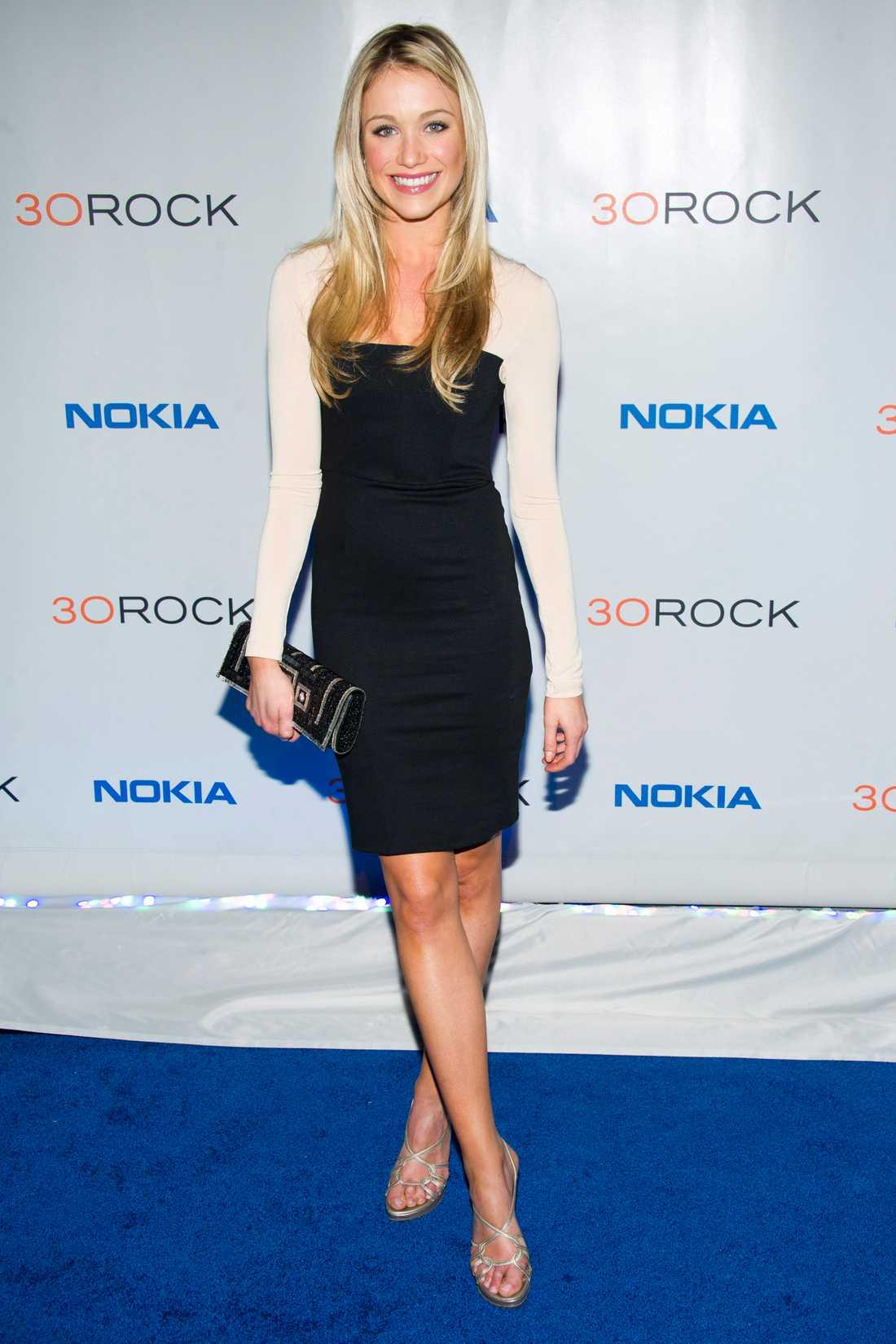 Skådisen Katrina Bowden i svartvitt fodral, glänsande klackar och glitterclutch.