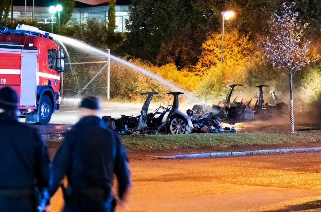 Polis och räddningstjänst på plats vid vraken efter de utbrända elbilarna utanför Teslas servicecenter i Malmö tidigt på tisdagsmorgonen.