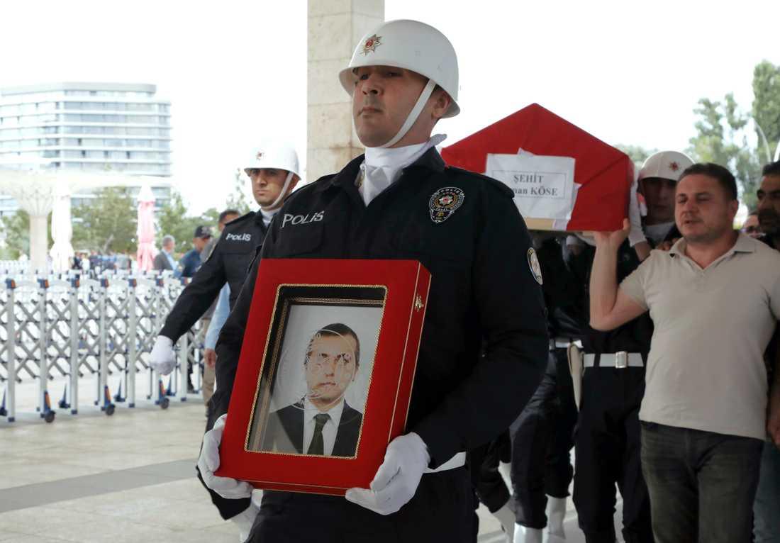 En polis bär en bild av den turkiske diplomaten Osman Köse som mördades i Erbil i Irak inför begravningen i Turkiets huvudstad Ankara.
