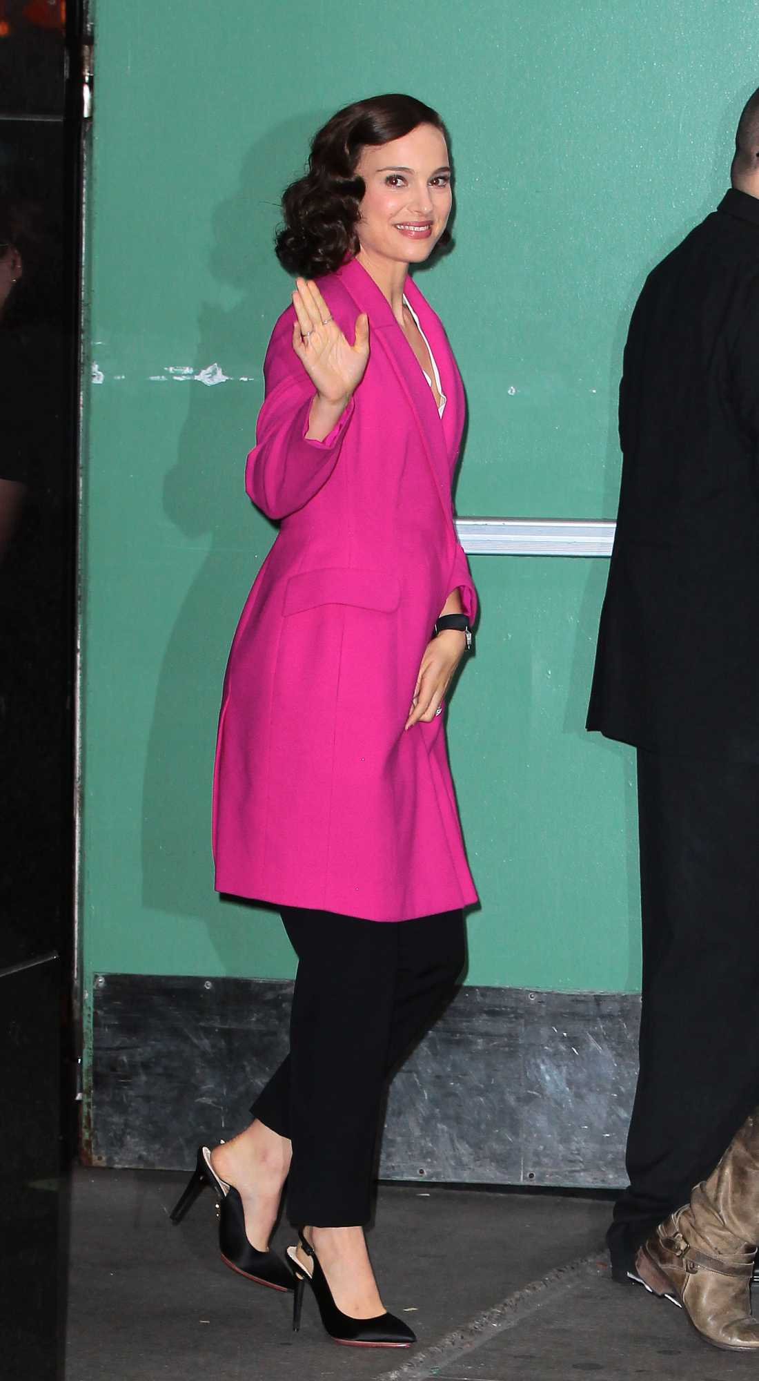 """Natalie Portman Natalie Portman fortsätter glänsa, här fortsatt i New York för tv-inspelning i fuchsia-färgad kappa, svarta byxor och pumps med öppen häl. Efter de senaste dagarnas klädval har det börjat ryktas att miss Portman kanske väntar smått igen. Kolla in gårdagens """"Dagen look"""" och avgör själv! Länk hittar du lite längre ner på sidan under """"Läs mer""""."""