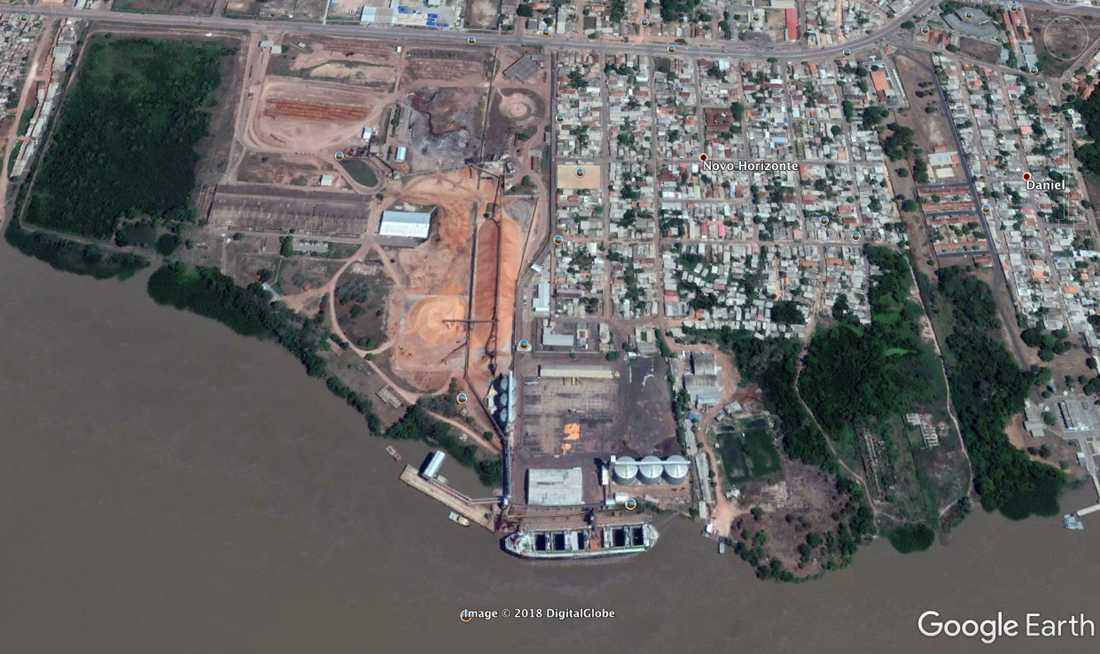 """I anläggningen """"Amapá Florestal e Celulose"""" som ägs av bolaget Amcel produceras flis som värmer upp stockholmarnas hem. På satellitbilder från hamnen syns hundratals meter långa rader trästammar, en större flistugganläggning samt massiva högar med träflis."""