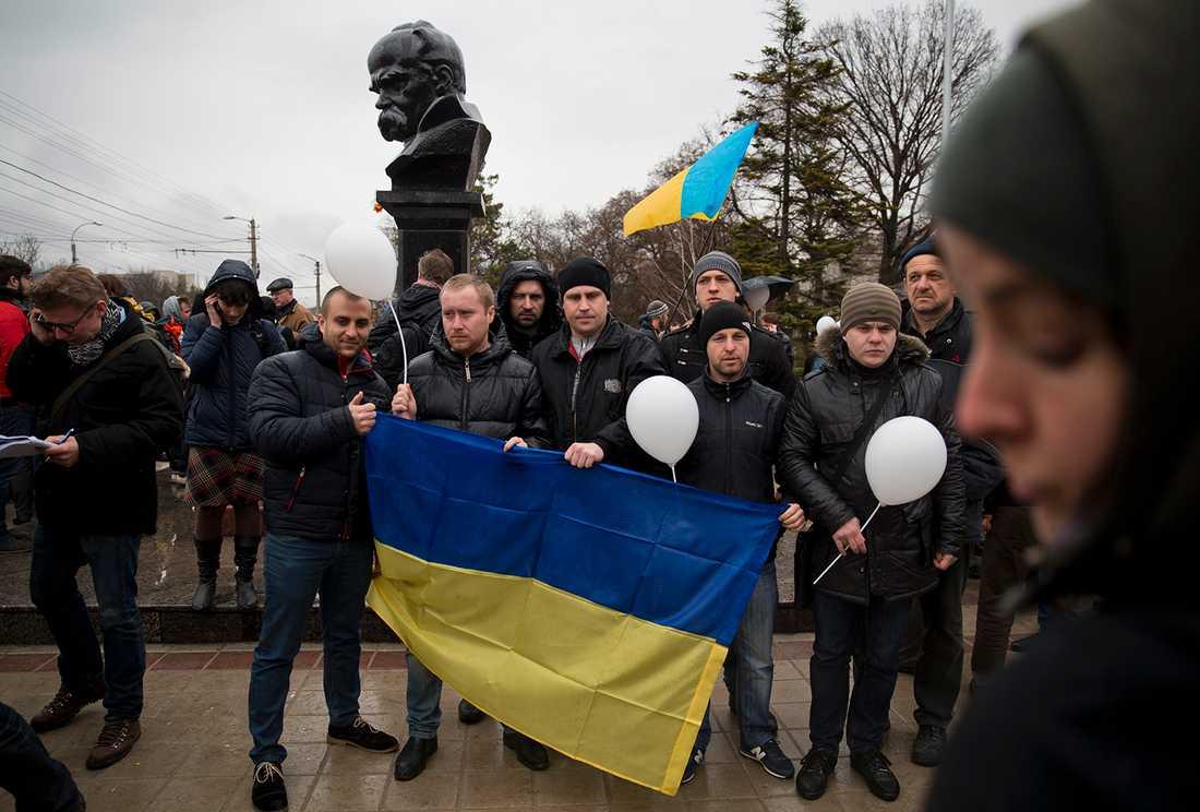 För Ukraina! Pro-Ukrainska demonstranter framför en staty av ukrainske poeten Taras Sjevtjenko i Simferopol, fredag 7 mars.