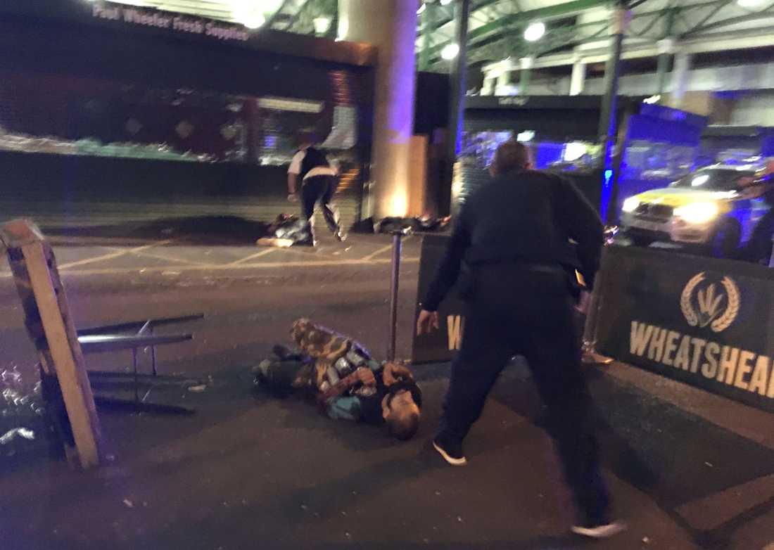 Beväpnad polis står vid de skjutna gärningsmännen utanför Borough Market, London 3 juni 2017.