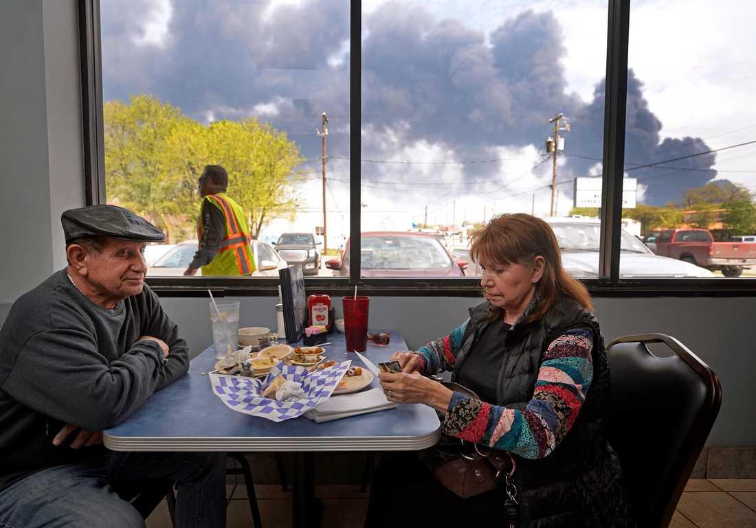 Charlie och Dalia Tamez äter lunch på en restaurang i amerikanska Houston, Texas, medan rök bolmar ut från branden.