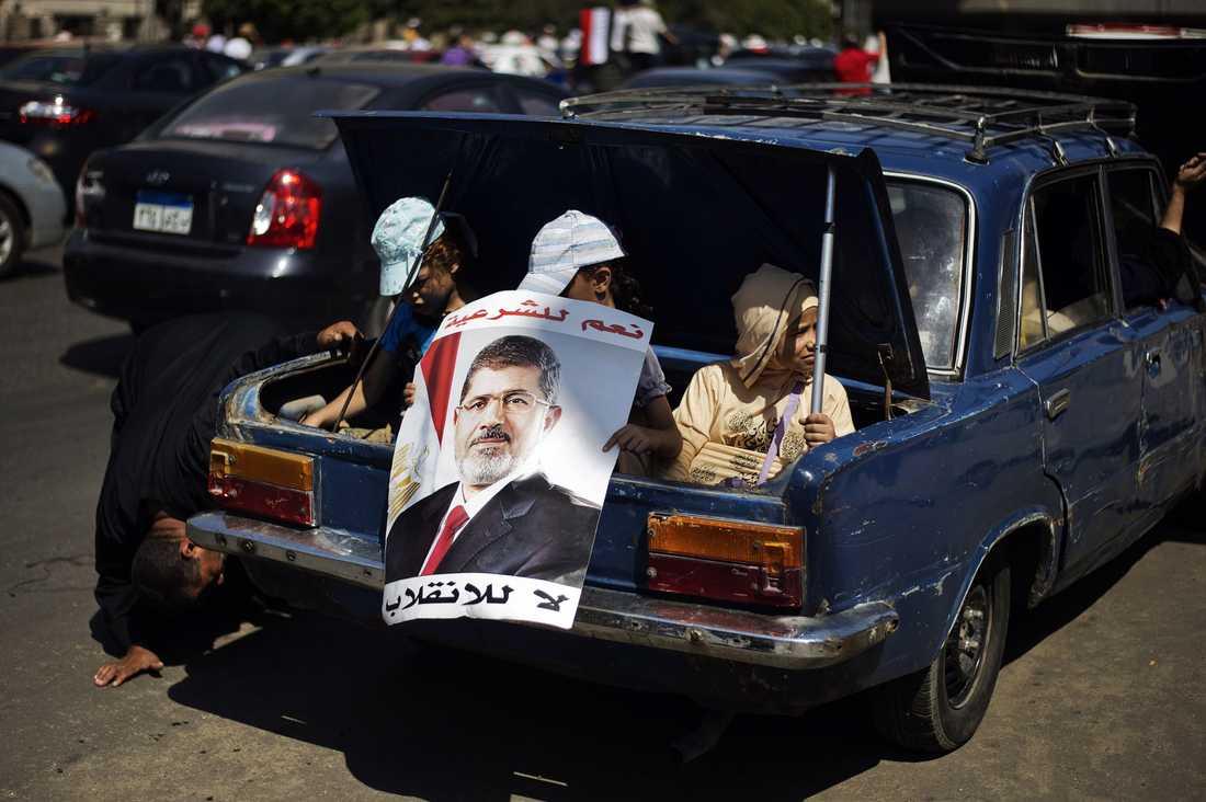 Egyptiska barn visar upp ett porträtt av avsatte presidenten Mursi under en demonstration till stöd för honom i Kairo.