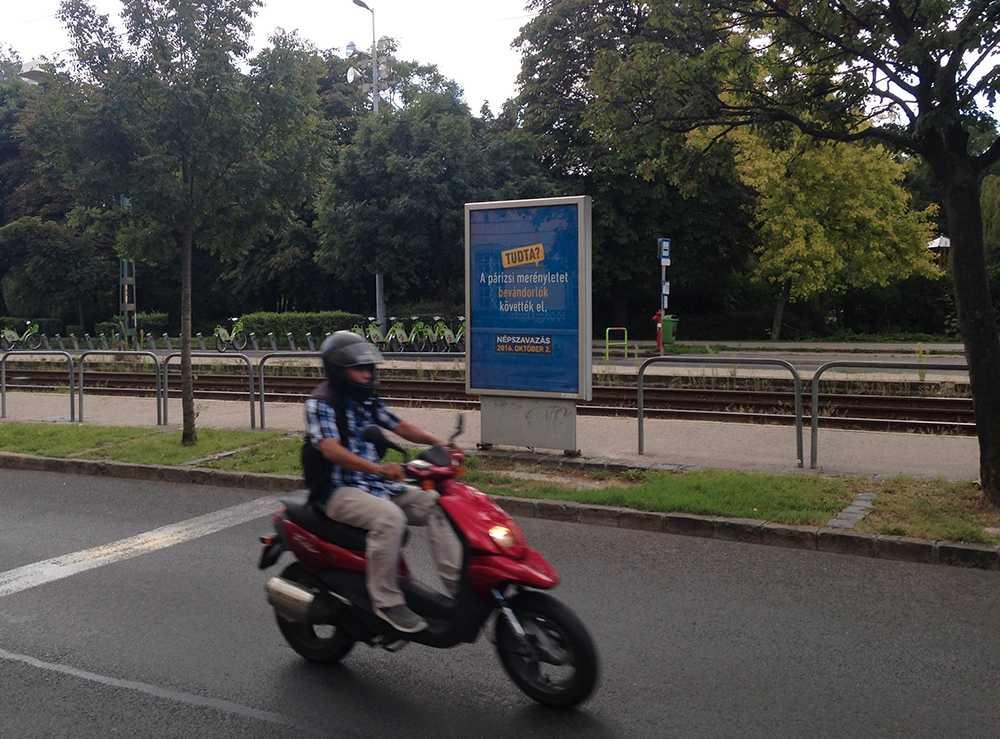 En mopedist kör förbi en av statens affischer. Foto: AP