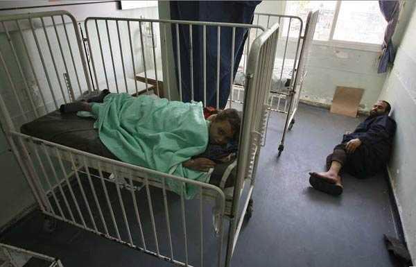 En pappa försöker att få lite sömn på Al Shifa-sjukhuset där hans skadade dotter vårdas.