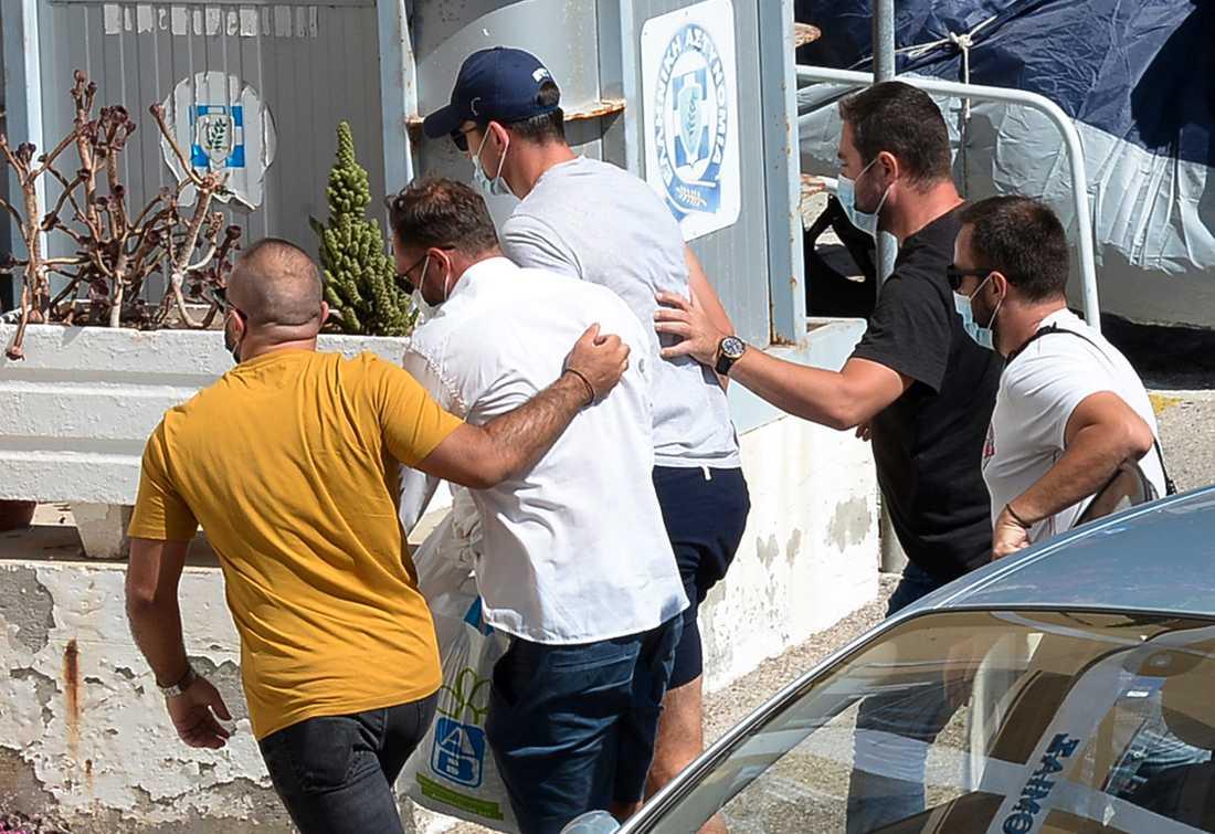 Harry Maguire eskorteras av civilpolis in på en polisstation.