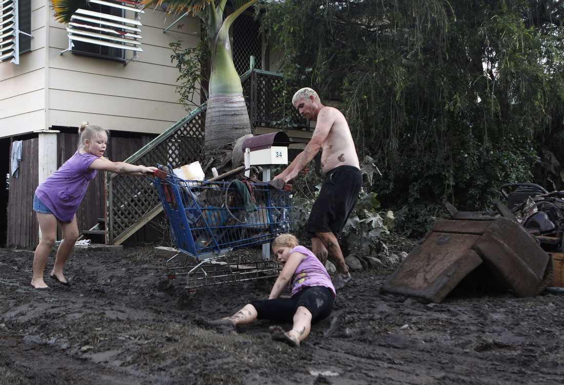 RÄDDAR SINA ÄGODELAR En liten flicka ramlar i leran under flytten av de få tillhörigheter som hennes syster och pappa räddat från sitt vattenskadade hus i Bundaberg i Queensland. Över 200 000 invånare har tvingats överge sina hus under översvämningarna.