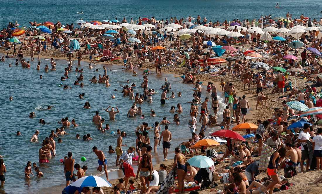 Människor säker svalka på stranden i Barcelona.