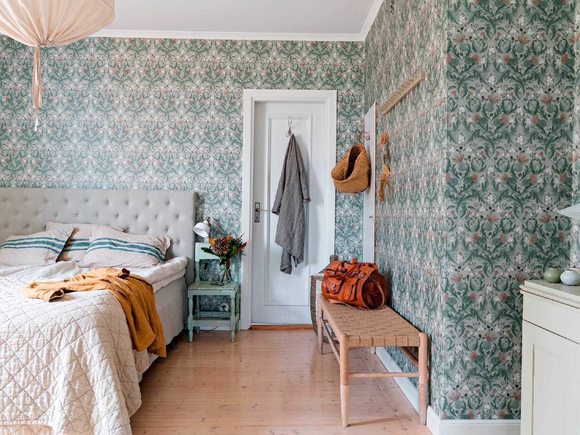 Fridas och Anders sovrum har fått en remake med tapeten Thistle från Boråstapeter som går i svala dämpade nyaser av grått och blågrönt.  Textilier i mjuka beige nyanser gör rummet harmoniskt och vilsamt.