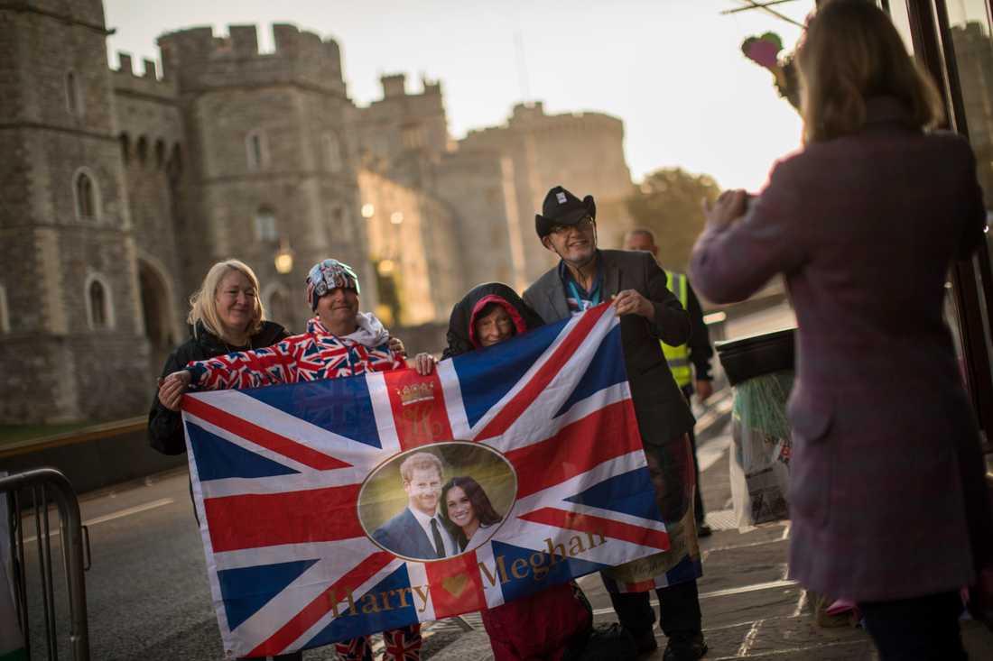 Glada bröllopsfirare håller upp den brittiska flaggan med Meghan Markle och prins Harry, utanför Windsor slott – där bröllopet hålls på lördagen.