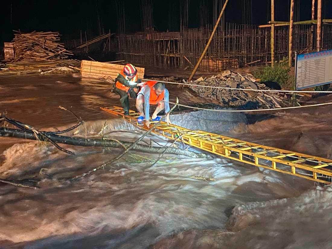 En räddningsarbetare hjälper en man att ta sig över ett översvämmat område i den kinesiska provinsen Jiangxi.