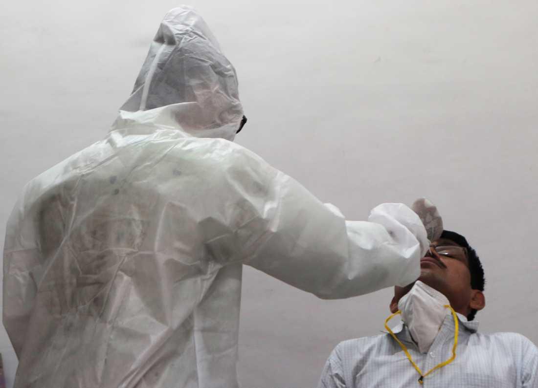 Vårdpersonal utför ett coronatest på en patient i Mumbai, Indien.