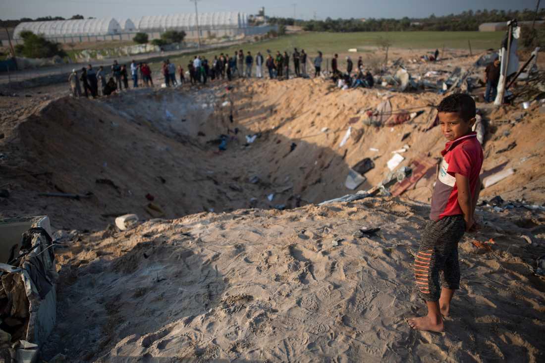 Människor som på torsdagen samlats kring kratern på Gazaremsan där Rasmi Abu Malhous bostad fanns innan den utsattes för en israelisk attack.