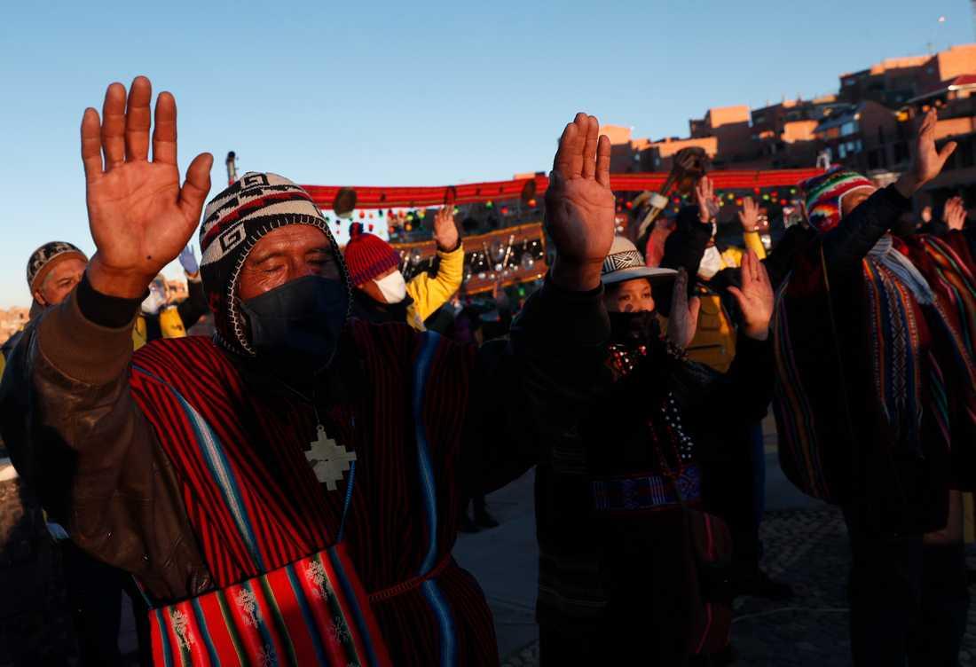 Människor tillhörande ursprungsfolket aymara bär skyddsmasker under en ceremoni för att fira solen i La Paz, Bolivia.