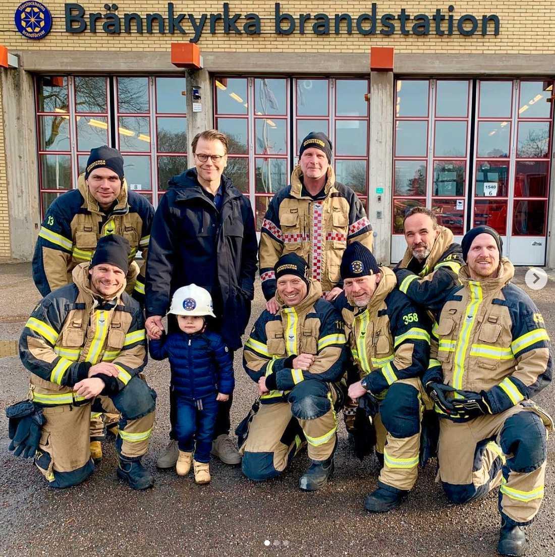 Här poserar prins Oscar och pappan prins Daniel med brandmännen på Brännkyrka brandstation.