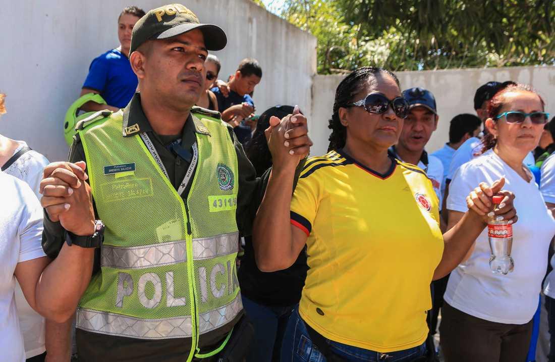 Poliser och anhöriga höll varandra i händerna under ceremonin.
