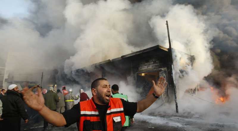 En palestinsk brandman framför ett brinnande hus på Gazaremsan efter att Israeliskt flyg avfyrat nya raketer på söndagsmorgonen.