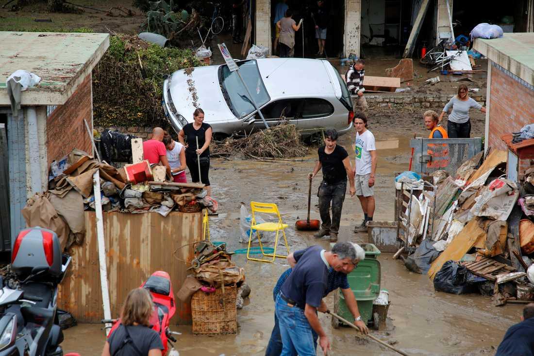 Boende i Livorno hjälps åt att röja upp efter översvämningarna.