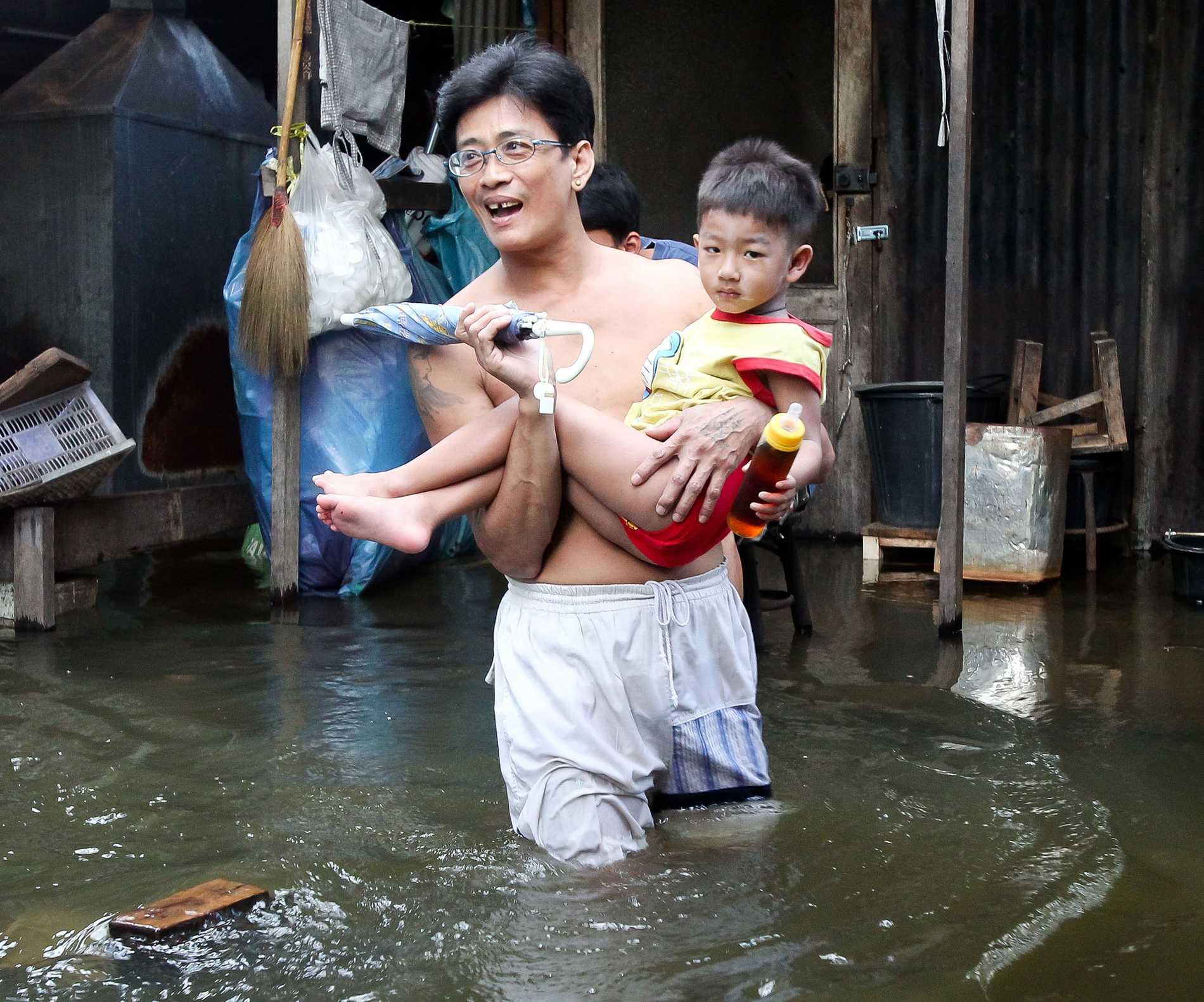 DRABBAS FÖRST. Far och son kämpar sig genom vattenmassorna i Bangkok i Thailand. Landet drabbades hårt av det kraftiga sommarregnet i slutet av förra året. Asien och Stillahavsområdet påverkas mest av klimatförändringarna.Foto: Dennis THERN