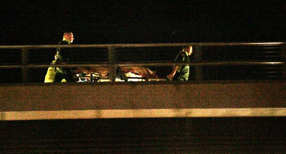 En av de skottskadade förs bort av ambulansmän.
